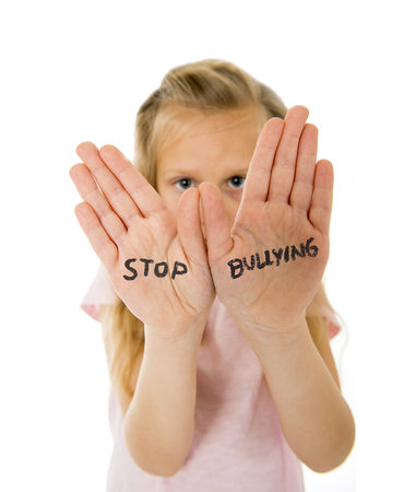 bullied: sweet and scared little schoolgirl showing the text stop bullying written in her hands in the concept children bullied and abused in school isolated on white background Stock Photo