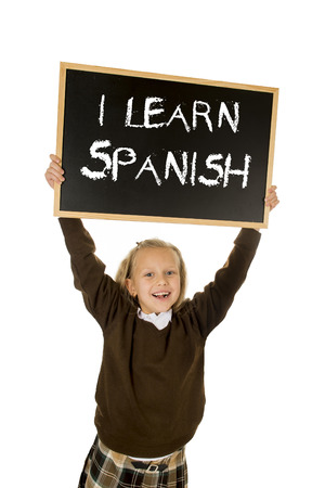 nine years old: 7  8 years old little beautiful blond schoolgirl smiling happy and cheerful holding and showing small blackboard with text I learn Spanish in language education concept isolated white