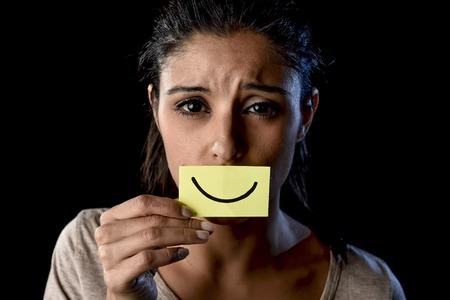junge schöne Latin traurig und deprimiert Latein Girl holding Papier versteckt ihren Mund hinter einem gefälschten gezeichneten Lächeln vorgibt, glücklich in Depressionen Konzept auf schwarzem Hintergrund isoliert