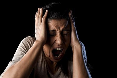 close-up portret jonge aantrekkelijke Latijns-vrouw wanhopig en bang geïsoleerd op zwarte achtergrond op zoek terrorized en horrified schreeuwen in oerdood emotie emotie gezicht Stockfoto