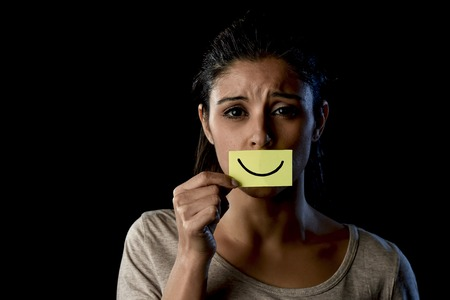fake smile: young beautiful Latin sad and depressed latin girl holding paper hiding her mouth behind a fake drawn smile pretending to be happy in depression concept isolated on black background