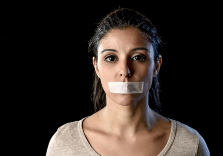 silenced: close up portrait of young attractive woman with mouth and lips sealed in adhesive tape restrained and abused censored and banned to speak and express opinion in freedom concept Stock Photo