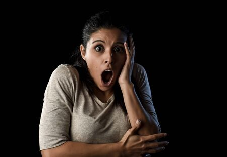 terrorized: close up portrait young attractive Latin woman screaming desperate and scared isolated on black background looking terrorized and horrified in primal fear emotion face expression Stock Photo