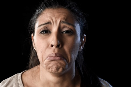 face expressions: young attractive sad and desperate Latin woman crying frustrated suffering pain and problems grieving in stress and sorrow in facial expression of sadness emotion isolated on black background