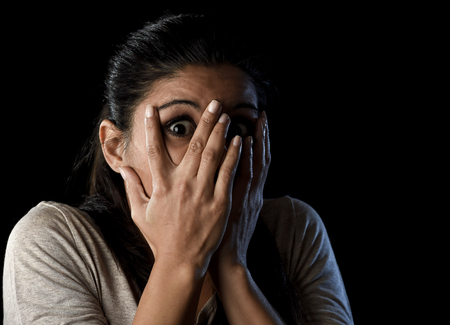 terrorized: close up portrait young attractive Latin woman desperate and scared isolated on black background looking terrorized and horrified covering her eyes in primal fear emotion face expression Stock Photo