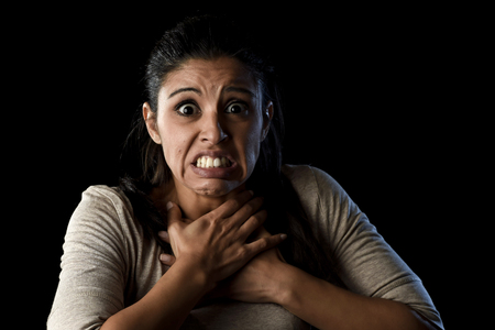 terrorized: close up portrait young attractive Latin woman desperate and scared isolated on black background looking terrorized and horrified in primal fear emotion face expression