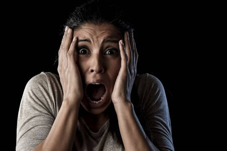 terrorized: close up portrait young attractive Latin woman desperate and scared isolated on black background looking terrorized and horrified screaming in primal fear emotion face expression