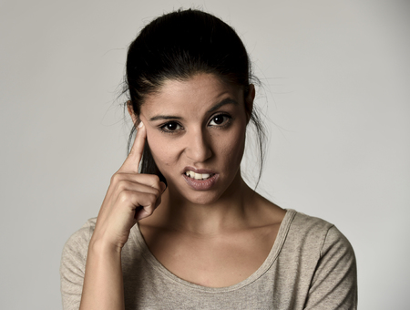 young beautiful arrogant and moody spanish woman showing negative feeling and contempt facial expression isolated on grey background looking cocky and defiant