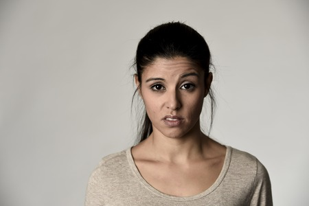 desprecio: young beautiful arrogant and moody spanish woman showing negative feeling and contempt facial expression isolated on grey background looking cocky and defiant
