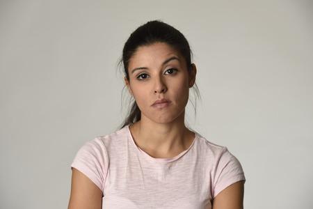若い傲慢と不機嫌そうなラテン美人探して生意気で反抗的な灰色の背景上に分離する負の感と軽蔑顔の表情を見せて