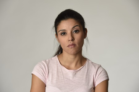 young beautiful arrogant and moody latin woman showing negative feeling and contempt facial expression isolated on grey background looking cocky and defiant