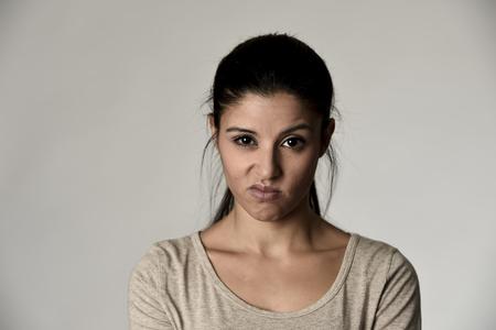 若い美しい傲慢と不機嫌そうなヒスパニック系女性探して生意気で反抗的な灰色の背景上に分離する負の感と軽蔑顔の表情を見せて