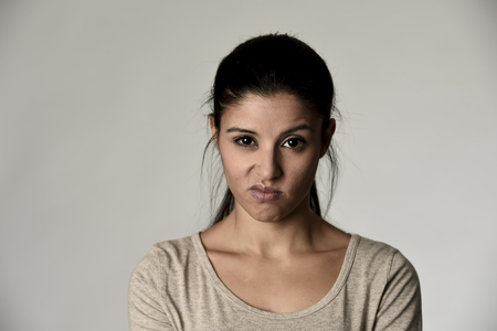 young beautiful arrogant and moody hispanic woman showing negative feeling and contempt facial expression isolated on grey background looking cocky and defiant