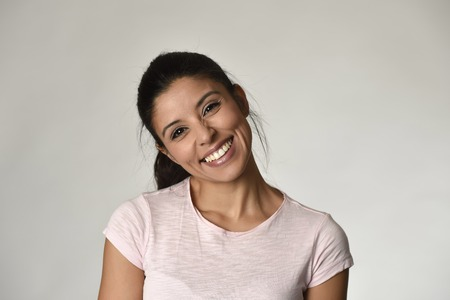 portrait of young beautiful and happy Latin woman with big toothy smile excited and cheerful in charming face expression isolated clear grey background in female happiness emotion