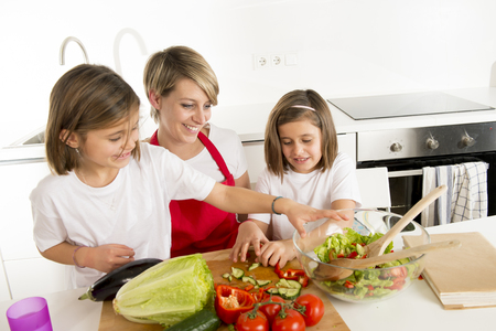 twin house: young mother in cook apron and sweet beautiful twin daughters cooking preparing together salad playful at home kitchen in healthy vegetable nutrition and homecook concept