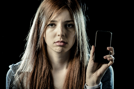 teenager girl or young woman holding mobile phone as internet stalked victim abused in cyberbullying or cyber bullying stress concept and in smartphone and network addiction concept Stock Photo
