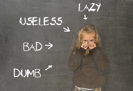 avergonzado: little beautiful blond schoolgirl sad ashamed and embarrassed being pointed and marked on school class blackboard with the words lazy useless bad and dumb in abuse discipline concept Foto de archivo
