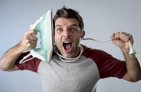 unskilled: young crazy desperate and frustrated man doing housework holding iron against his face and cable stressed and confused in unskilled and unable male for ironing isolated on even background Stock Photo