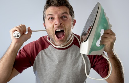 unskilled: young crazy desperate and frustrated man doing housework holding iron and cable stressed and confused in unskilled and unable male for ironing isolated on even background