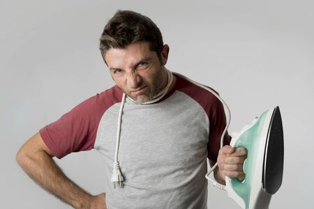 unskilled: young crazy desperate and frustrated man doing housework holding iron stressed and confused in unskilled and unable male for ironing isolated on even background Stock Photo