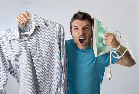 unskilled: young attractive and frustrated man holding iron and shirt stressed and tired in bored and lazy face expression in male ironing going wrong and domestic work concept isolated even background