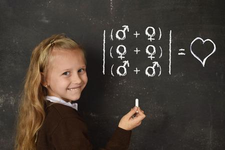 belle jeune écolière douce blonde en uniforme craie tenant debout écrit sur tableau noir pour la liberté d'orientation sexuelle amour de soutien pour les couples hétérosexuels et homosexuels