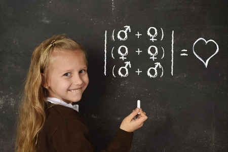 young beautiful blond sweet schoolgirl in uniform holding chalk writing on blackboard standing for freedom of sexuality orientation supporting love for heterosexual and homosexual couples Stockfoto