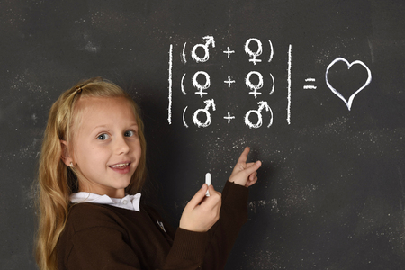 young beautiful blond sweet schoolgirl in uniform holding chalk writing on blackboard standing for freedom of sexuality orientation supporting love for heterosexual and homosexual couples Stock Photo