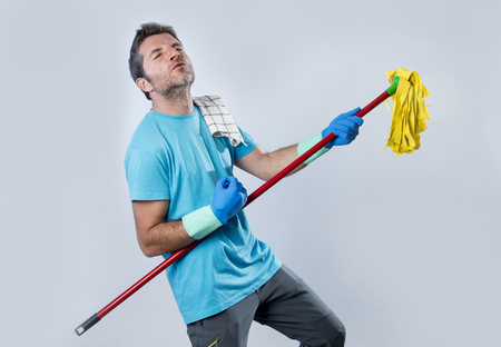 air cleaner: young domestic service man or happy husband cleaning home playing with mop a song on air guitar having fun enjoying isolated on even background in housekeeping and home cleaning concept