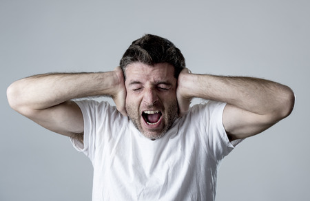 hands covering ears: young attractive man sad and depressed suffering depression feeling sorrow and pain screaming desperate covering ears with hands in sadness emotion concept Stock Photo