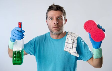 portrait of domestic service man or tired husband angry and stressed doing house cleaning with spray bottle and sponge in annoyed and busy face expression isolated even background Stock Photo