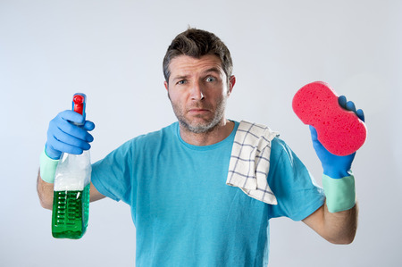 servicio domestico: portrait of domestic service man or tired husband angry and stressed doing house cleaning with spray bottle and sponge in annoyed and busy face expression isolated even background Foto de archivo