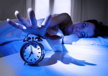 levantandose: shock upset young woman at home in bed not wanting to wake up turning off her alarm clock with a crazy look on her face and dramatic shadow light in getting up early morning concept