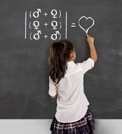sexualidad: young beautiful schoolgirl in uniform holding chalk writing on blackboard standing for freedom of sexuality orientation supporting love for heterosexual and homosexual couples