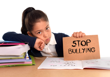bullied: young cute hispanic schoolgirl scared in stress holding paper with text stop bullying written looking desperate asking for help sitting at school desk alone in victim children bullied abuse concept Stock Photo
