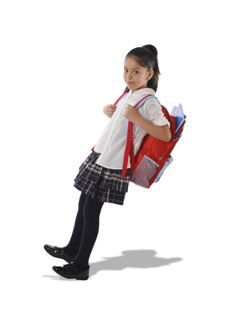 overweight kid: sweet little girl carrying very heavy and big backpack or huge schoolbag full of school books causing her leaning and falling on her back due to overweight isolated on white background Stock Photo
