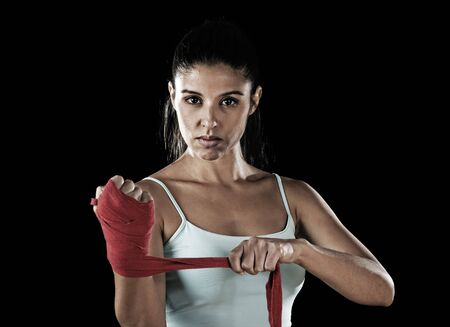 young attractive hispanic fitness woman doing self hand wraps before boxing or fighting workout isolated on black background looking fierce concentrated and confident