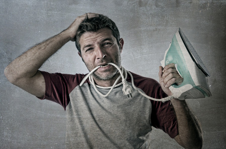 unskilled: young crazy desperate and frustrated man doing housework holding iron and cable in mouth stressed and confused in unskilled and unable male for ironing isolated on even background
