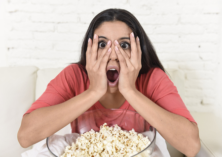 suspenso: young beautiful latin woman sitting at home sofa couch in living room watching television scary horror movie or horrible news scared and excited covering her eyes eating popcorn Foto de archivo
