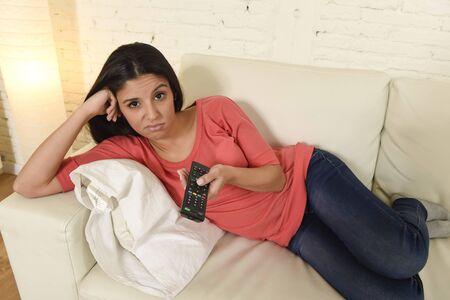 changing channels: young beautiful hispanic woman lying at home sofa couch in living room watching television looking tired and bored disappointed holding remote control in negative emotion