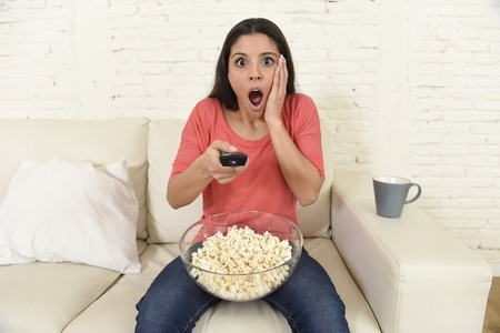 suspense: young beautiful latin woman sitting at home sofa couch in living room watching television scary horror movie or horrible news scared and excited holding remote control eating popcorn