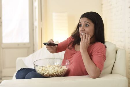 watching horror: young beautiful latin woman sitting at home sofa couch in living room watching television scary horror movie or horrible news scared and excited holding remote control eating popcorn