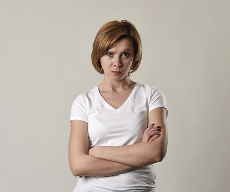 pissed: young attractive and moody woman posing alone angry and upset in bad mood and rage face expression isolated on grey background looking defiant and pissed off