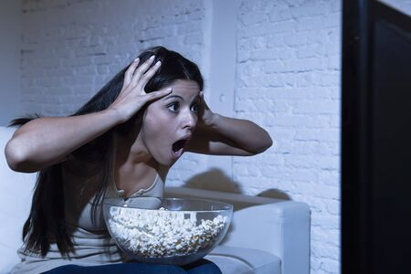 suspense: young Spanish woman at home sofa couch in living room watching television scary horror movie or suspense thriller film or horrible news scared and excited  in panic eating popcorn bowl