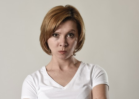 young attractive and moody woman posing alone angry and upset in bad mood and rage face expression isolated on grey background looking defiant and pissed off