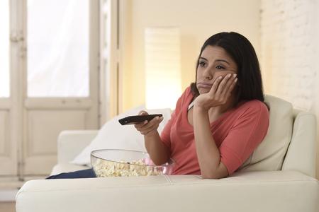 junge schöne liegend latina Frau zu Hause Sofa Couch im Wohnzimmer Fernsehen sah müde und gelangweilt enttäuscht Fernbedienung in negative Emotionen halten Standard-Bild