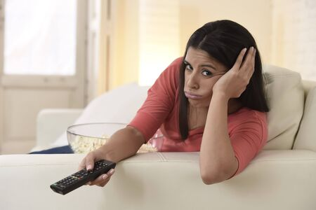young beautiful latina woman lying at home sofa couch in living room watching television looking tired and bored disappointed holding remote controller in negative emotion