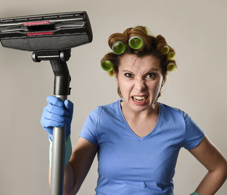 young angry and frustrated maid service woman or upset housewife with hair rollers cleaning gloves holding vacuum cleaner stressed in housework and housekeeping stress concept Imagens