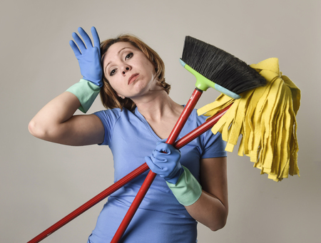 young attractive stressed service woman in washing rubber gloves carrying cleaning broom and mop frustrated and overworked looking tired and lazy in housework stress and housekeeping
