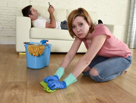 young couple with woman or wife kneeling washing and cleaning the floor scrubbing and man or husband lying on couch relaxed not giving her help in chauvinism and sexism concept